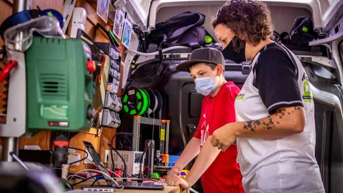 In einem umgebauten Bus stehen ein Kind und eine Frau mit Mund-Nasen-Schutz neben einem 3D-Drucker und einem Laptop.