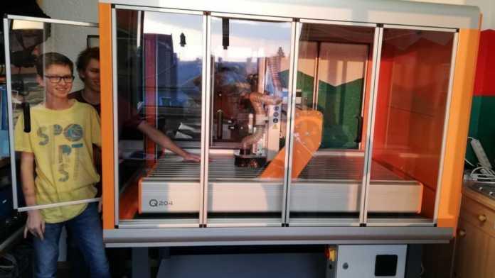 Zwei Kinder stehen neben einer CNC-Fräse im Glasgehäuse.