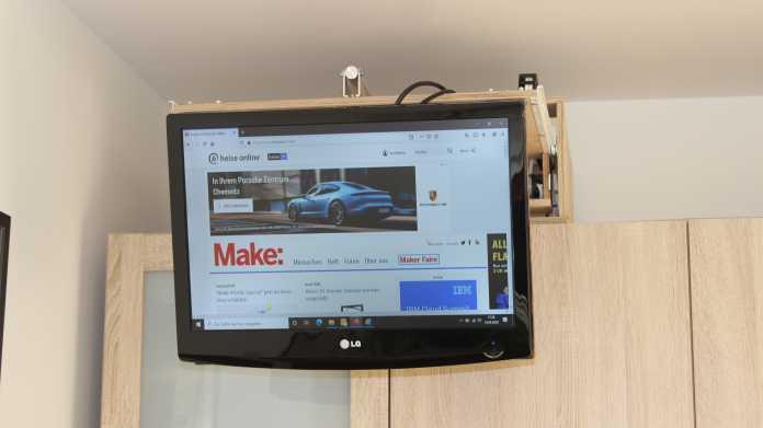 Ein Fernsehmonitor hängt vor einem Schrank, er ist an einer Schublade auf dem Schrank befestigt.
