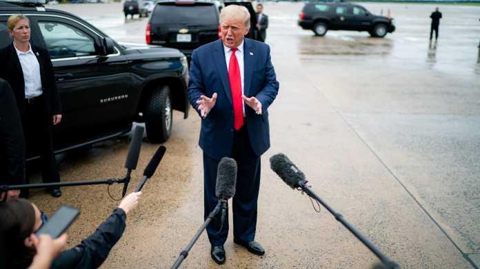 Donald Trump auf einem Rollfeld in Mikrofone sprechend