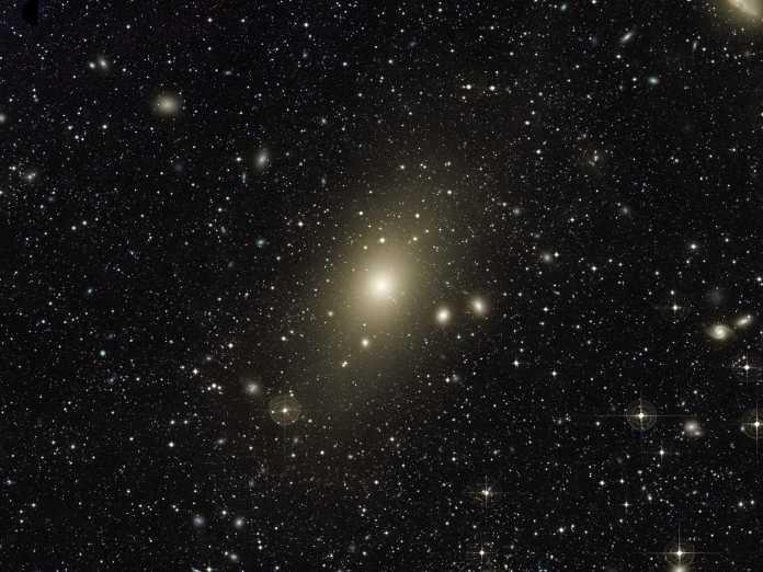 Lang belichtete Aufnahme der elliptischen Riesengalaxie Messier 87 (M87) mit einigen benachbarten Galaxien im Virgo-Galaxienhaufen. Die lange Belichtung mit dem 61 cm Burrell Schmidt Telescope enthüllt den optischen Teil des Halos um die Galaxie, in dem sich versprengte Sterne aus früheren Kollisionen aufhalten, die ihn zum Leuchten bringen. ⅚ der Masse der Galaxie stecken als unsichtbare Dunkle Materie gleichermaßen in diesem Halo. Die meisten scharfen Punkte im Bild sind Vordergrundsterne aus der Milchstraße. Bei vielen der um die Galaxie gehäuft vorhandenen, in Großansicht gerade noch wahrnehmbaren Lichtpunkte handelt es sich um einige der 12.000 Kugelsternhaufen der Galaxie.
