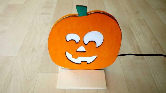 Ein orange angemalter Kürbis aus Sperrholz, mit Aussparungen für Mund, Nase und Augen, dahinter ein weißes Papier.