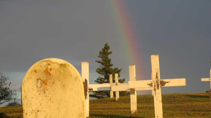 Weißer Grabstein, weiße Kreuze, dahinter ein Regenbogen