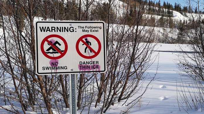 Warnschild vor verschneitem See verbietet Schwimmen und warnt vor dünnem Eis