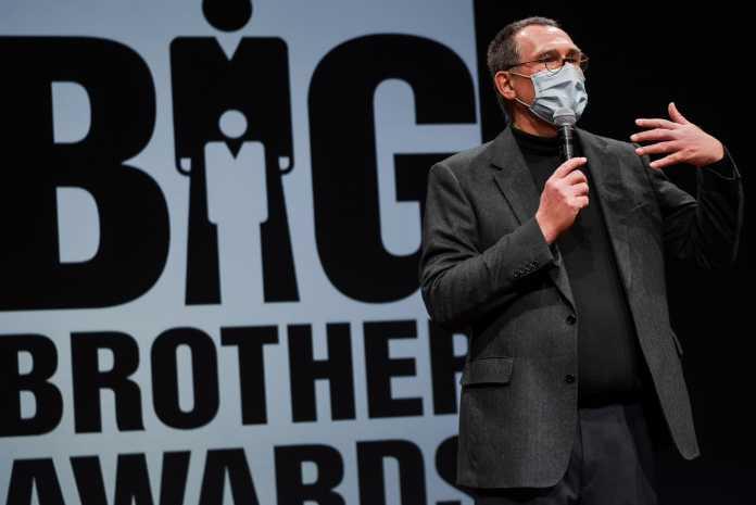 """Georg Markus Kainz mit Maske, dahinter Schriftzug """"Big Brother Awards"""""""