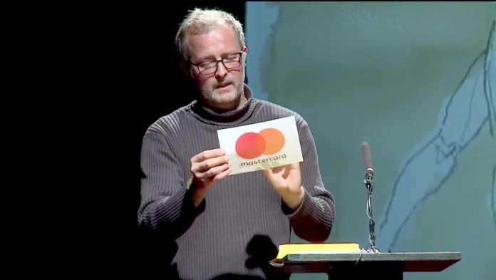Mann hält Zettel mit Mastercard-Logo