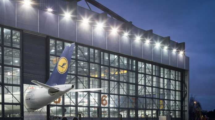 Ein Wartungshangar der Lufthansa-Werft in Hamburg: Der Airbus A340 ist zu lang für die Halle, das Flugzeugheck ragt bei geschlossenen Hallentoren durch eine spezielle Öffnung heraus. Die Belichtung orientiert sich an der Beleuchtung im Inneren der Halle, dadurch wird der Zweck des Hangars überhaupt erst sichtbar. Tagsüber reicht die Beleuchtung im Inneren nicht aus, der Hangar wirkt dann dunkel, denn zusätzlich versperren die spiegelnden Scheiben den Blick. Der blaue Nachthimmel passt hier ideal zum Logo am Leitwerk. Die Wahl einer kleinen Blendenöffnung erzeugt die Sterncheneffekte der Außenbeleuchtung.Canon EOS 5D Mark III  45 mm  ISO 200  f/11  2,5 s