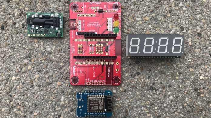 Eine rote Platine, daneben ein grüner CO2-Sensor, eine 7-Segment-Anzeige und ein Wemos D1.