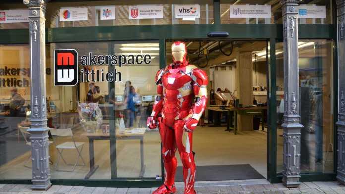 """Iron Man in roter Rüstung vor einer Glaswand mit Aufschrift """"Makerspace Wittlich"""". Dahinter sind Geräte eines Makerspaces zu erkennen."""