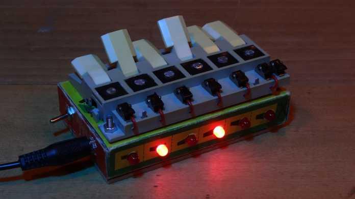 Ein Kästchen mit weißer Tastatur, einige Tasten sind nach oben gestellt.