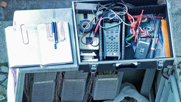 Werkzeugkoffer eines Telekommunikationstechnikers auf einem offenen Kabelverzweigergehäuse der Deutschen Telekom.