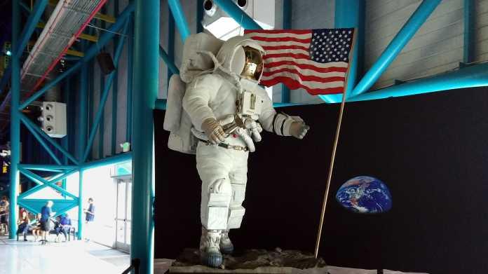 Lebensgroße Figur in Astronautenanzug, daneben eine US-Flagge