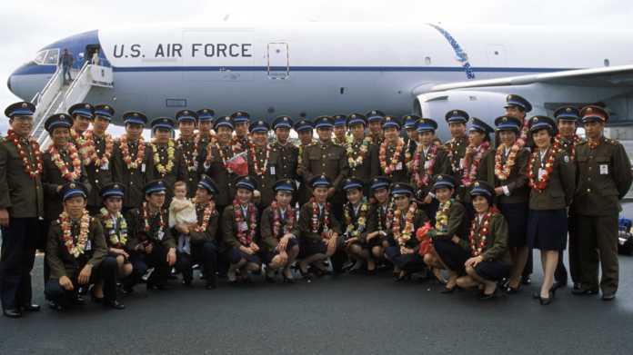 Gruppenfoto chinesischer Soldatinnen und Soldaten, meist mit Leis, sowie ein Baby; dahinter ein Flugzeug der US Air Force