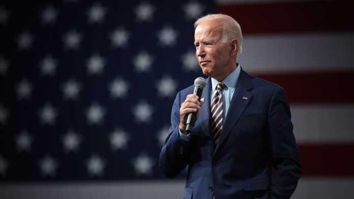Joe Biden mit Mikrofon, im Hintergund eine US-Fahne