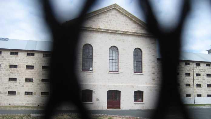 Gefängnisgebäude durch einen Metallzaun betrachtet