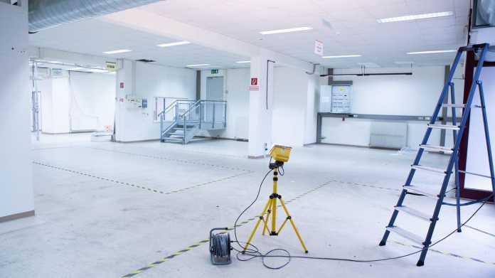 Blick in eine helle, leere Halle, an der Seite stehen eine Leiter und ein Baustrahler.