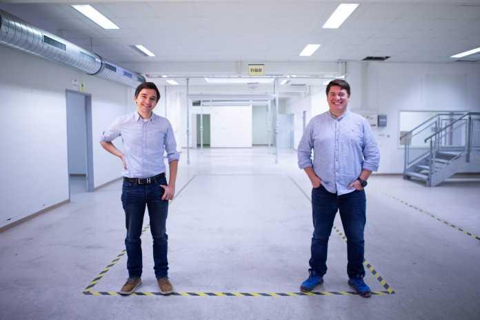 Zwei Männer stehen in einer leeren, hellen Halle.