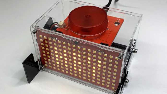 Ein transparenter Acrylkasten. Vorn ist eine LED-Matrix mit der Aufschrift HEY, oben ein roter Button.