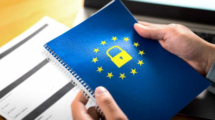 2 Hände halte ein blaues Heft worauf das Symbol der EU und ein gelbes Vorhängeschloss gedruckt sind