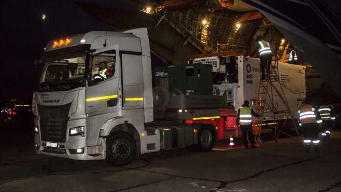 Sattelschlepper parkt vor einer geöffneten Antonov, aus der gerade ein Container mit Aufschrift OneWeb auf den Sattelschlepper verladen wird.