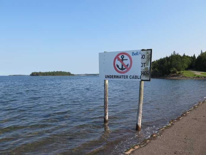 """Verbotsschild mit Symbol """"ankern verboten"""" und Aufschrift """"Underwater Cable"""" steht im Meerwasser nahe eines Strandes"""
