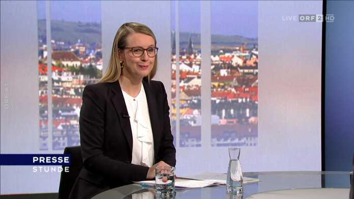 Margarete Schramböck an Tisch sitzend