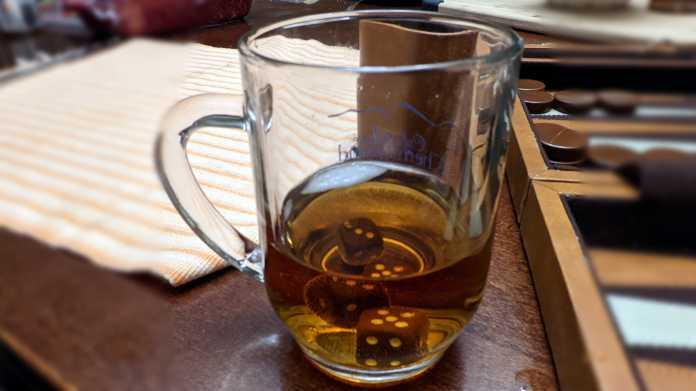 Teilweise mit Tee gefülltes Glas, darin liegen Spielwürfel