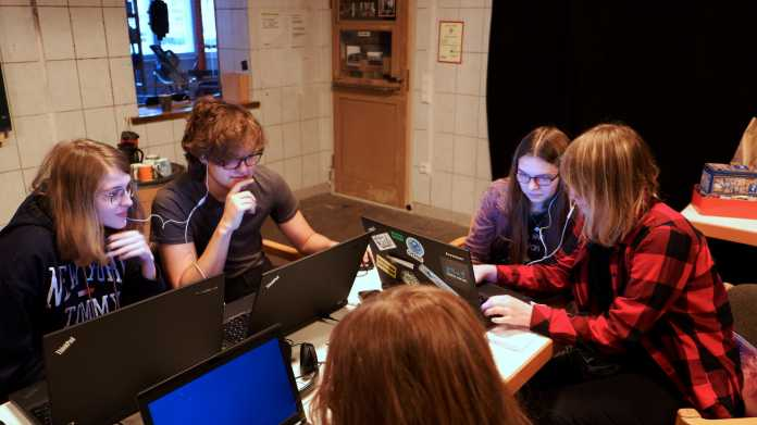 Fünf Jugendliche sitzen um einen Tisch und schauen auf Laptops.