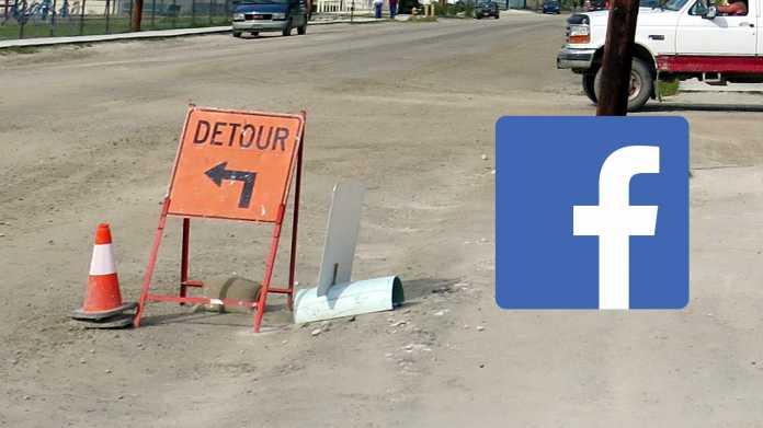 """Schild """"Detour"""" auf unbefestigter Straße - rechts danaben ein Facebook-Logo"""
