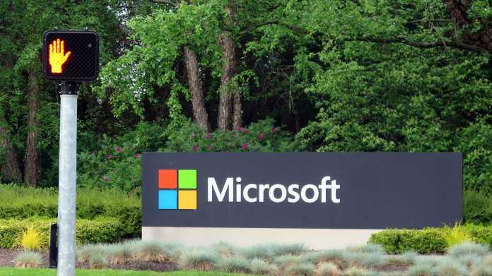 """Schild """"Microsoft"""" an Einfahrt zu Microsoft-Gelände, davor eine auf Rot stehende Fußgängerampel"""
