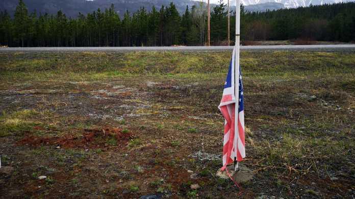 Eine US-Fahne hängt lahm am unteren Ende einer Fahnenstange und somit im nassen Erdreich