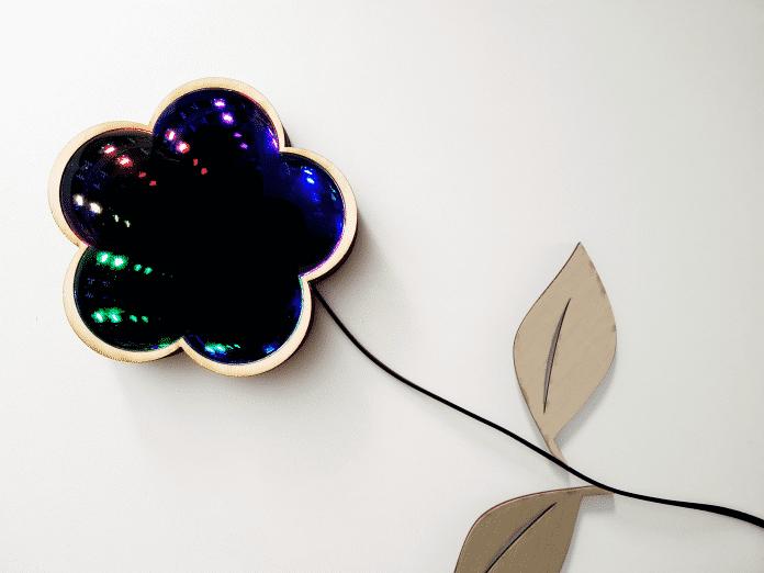 Ein Spiegel in Blütenform, in dem bunte LEDs in die Unendlichkeit gespiegelt werden. An dem Kabel sind Blumenblätter aus dem Lasercutter befestigt.