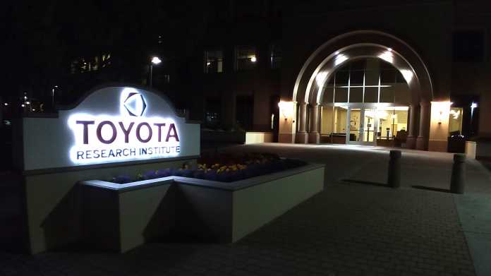 """Eingangsbereich mit beleuchtetem Schild """"Toyota Research Institute"""" bei Nacht"""