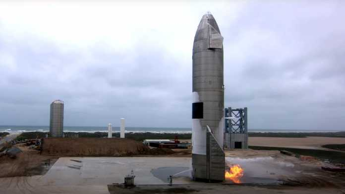 Aufrecht stehendes Starship, am Fuß Flammen