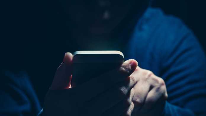 Symbolbild - ein umschatteter User hält ein Handy
