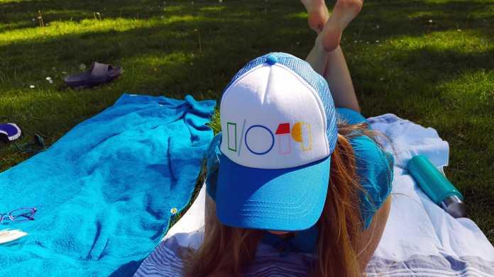 "Blonde Frau liegt im Gras, trägt mit Kappe mit ""I/O 19""-Logo"