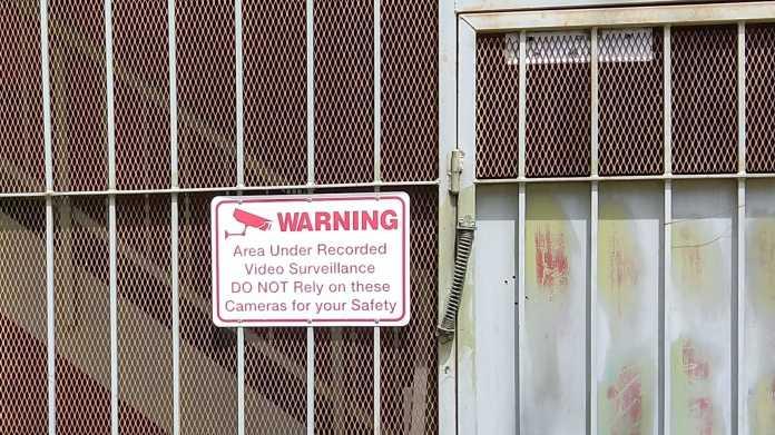 Gittertor mit Warnung vor Videoüberwachung, auf die man sich nicht verlassen möge