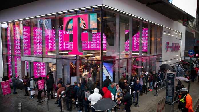 T-Mobile-Laden mit Glasfassade, davor Kundenschlange