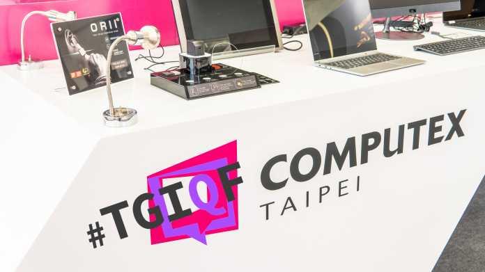 """Tisch mit Aufschrift """"#TGIQF Computex Taipei"""", darauf einige elektronischen Geräte"""