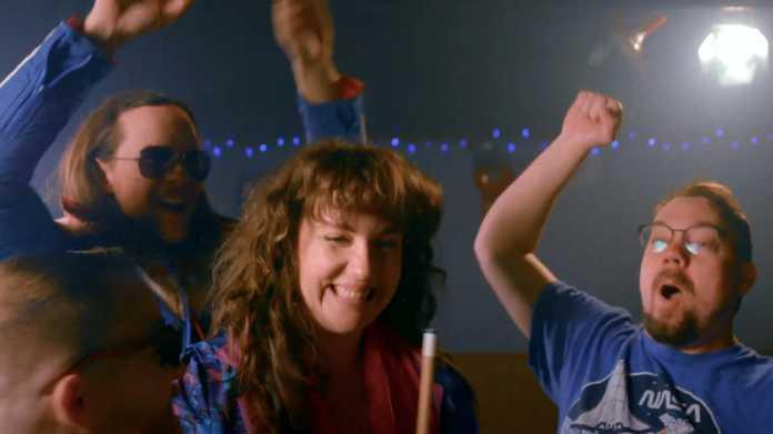Szene aus Musikvideo: Lächelnde Frau mit Queue, dahinter feiernde Männer