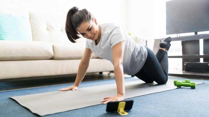 Frau bei Fitnessübungen auf Matte, im Vordergrund ein Handy