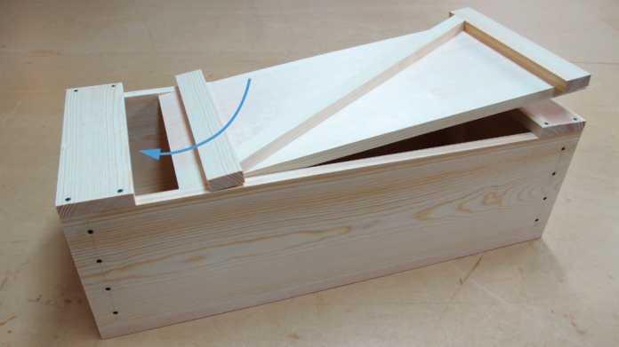 Schritt 1 beim Schließen der Kiste: Deckel schräg mit dem langen Anschlag unter das Endstück schieben.