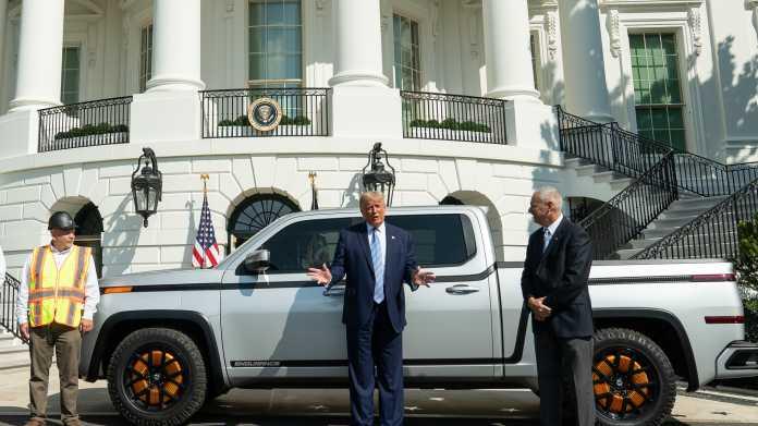 Donald Trump vor Pickup, dahinter das Weiße Haus