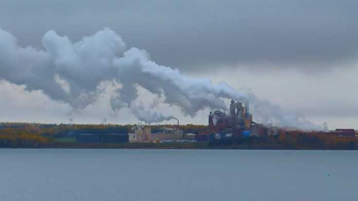 Stark Abgase ausstoßende Industrianlage am Ufer eines Flusses