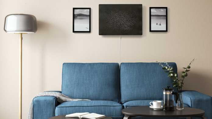 Wohnzimmerszene - schwarzer Lautsprecher hängt zwischen zwei Bildern an der Wand