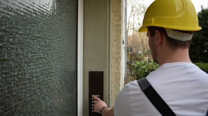 Mann mit Sicherheitshelm klingelt an Haustür