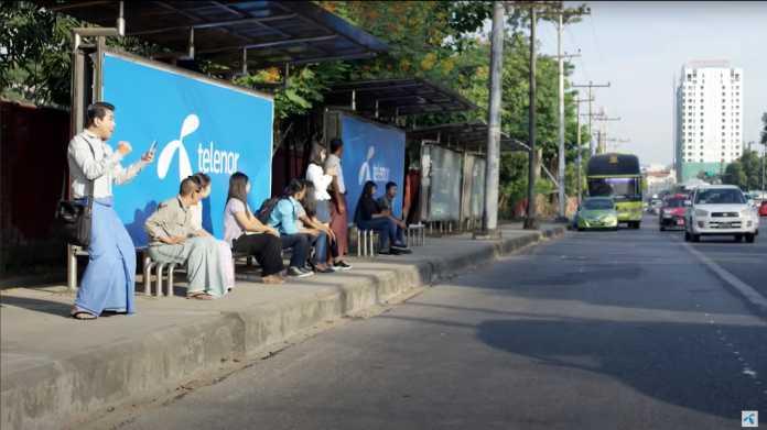 """Personen warten an Bushaltestelle, dort """"Telenor""""-Werbeplakate"""