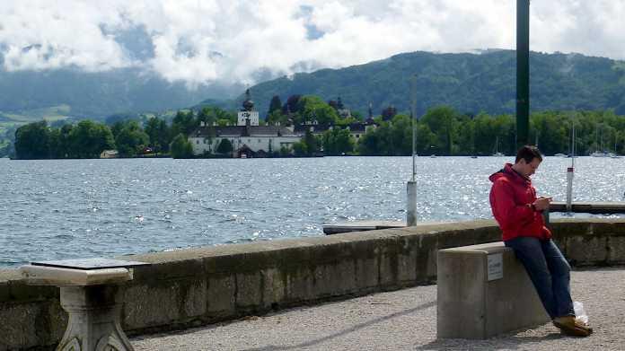 Traunsee - im Hintergrund Schloss Orth, im Vordergrund ein Mann in roter Jacke ein Handy bedienend