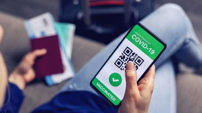 Person mit Reisepass und digitalem Impfnachweis in einer Smartphone-App wartet auf dem Flughafen.