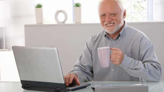 Senior mit Kaffeetasse am Notebook